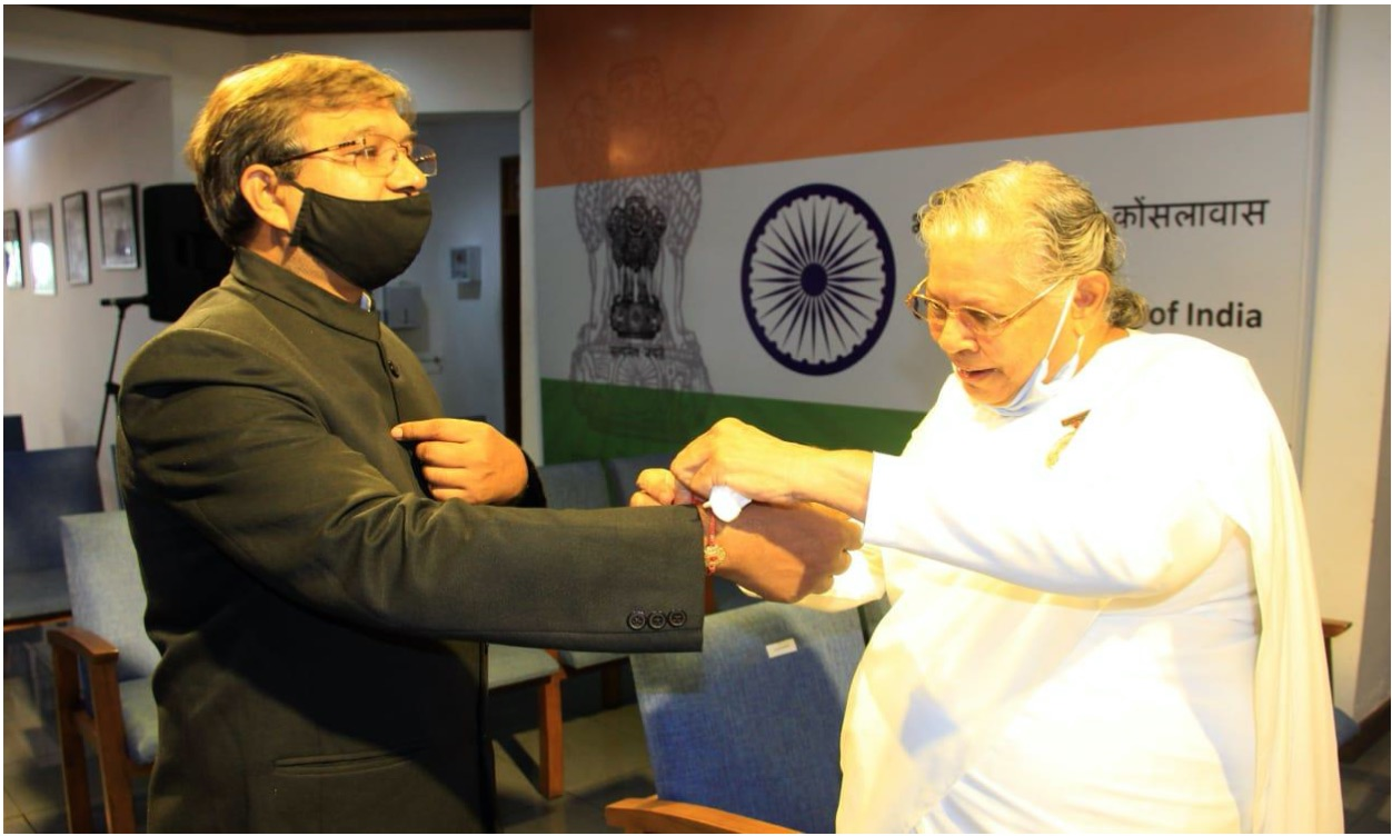 B. K. Sister Janaki tying a Rakhi on the wrist of H. E. the Consulate General Mr. Prakash Chand.